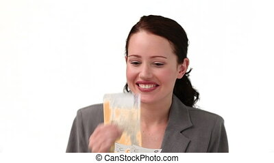 Brunette woman in suit smelling money isolated on a white...