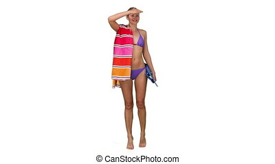 Woman in swimsuit looking for someone on the beach