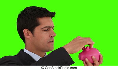Dark-haired businessman saving up money against a green...