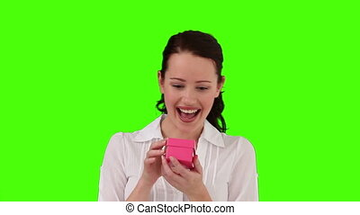 Brunette woman very happy to receive a gift against a green...