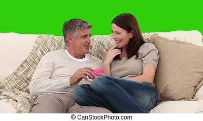 Retired man giving a gift to his wife on the sofa