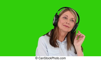 Mature woman listening to music with a headphones against a...