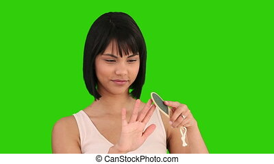 Asian woman filling her nails - Chroma-key footage of an...