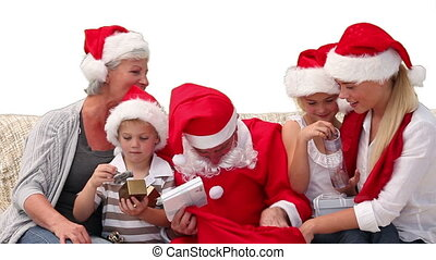 Santa Claus giving gifts to a family on a sofa