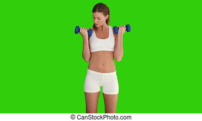 Cute female doing exercise with dumbbells against a green...