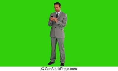 Businessman in  a gray suit writing a text on his phone