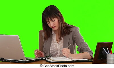 Businesswoman calculating her bills at her desk - Chromakey...
