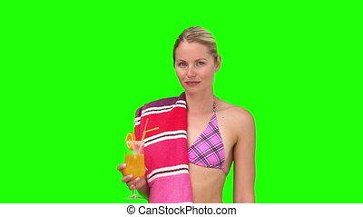 Blond woman in a purple swimsuit drinking a cocktail because she is feeling too hot