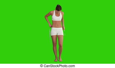 Woman in sportswear measuring her belly against a green...