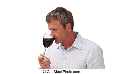 Elderly man enjoying a glass of red wine
