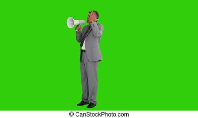 Mature businessman giving orders with a megaphone against a...