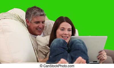 Mature couple using a laptop on their sofa against a green...