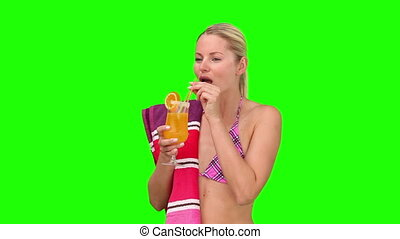 Woman in purple swimsuit sipping a cocktail against a green...