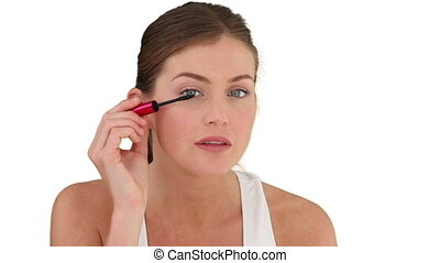 Dark-haired woman putting on make up