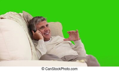 Retired man talking on the phone in the living room