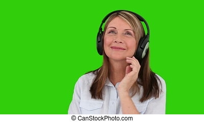 Elderly woman listening to music with headphones against a...
