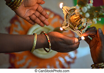 hands lighthing oil lamp during deepavali ceremony