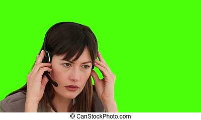 Brunette woman speaking over the headset against a green...