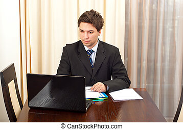 Young business man working on laptop and sitting on chair at...