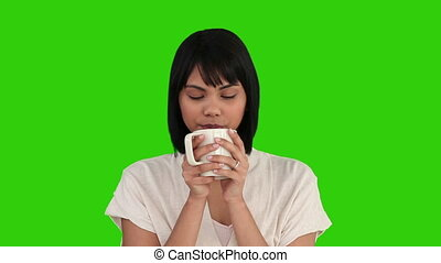 Asian woman drinking a cup of tea - Chroma-key footage of an...