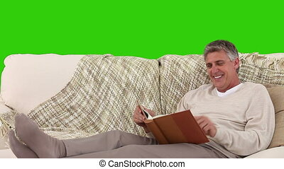 Casual retired man looking at an album on his sofa
