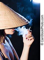 woman in the Vietnamese hat smoking a cigarette