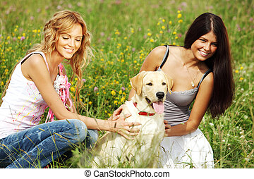 girlfriends and dog in green grass field