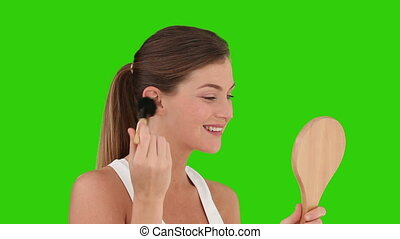 Brown-haired woman putting on make-up against a green screen