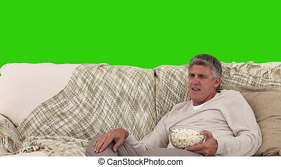 Retired man watching tv with popcorns against a green screen