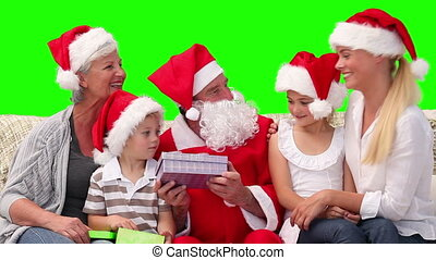 Santa Claus offering gifts to a family - Chromakey footage...