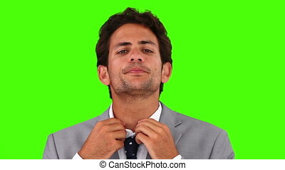 Young businessman putting on his tie against a green screen
