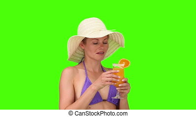 Woman in purple swimsuit with an hat sipping a cocktail