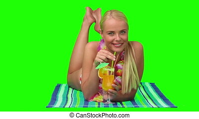 Blond woman sipping a cocktail on the beach against a green...