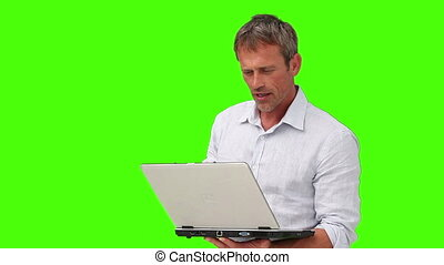 Casual man in shirt holding his laptop