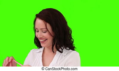 Dark-haired woman putting on a scarf against a green screen