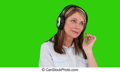 Eldery woman listening to music with a headphones against a...