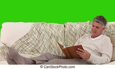 Retired man looking at an album in his sofa - Chromakey...