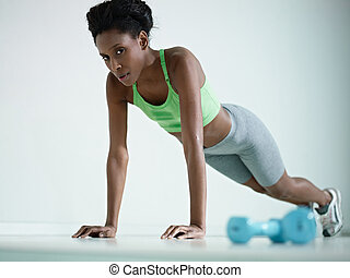 african woman doing series of push-ups in gym - young...
