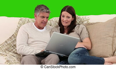 Elderly couple using a laptop on a sofa