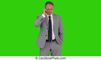 Mature businessman in  a gray suit having a phone call