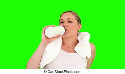Pretty pregnant woman drinking water after sport -...