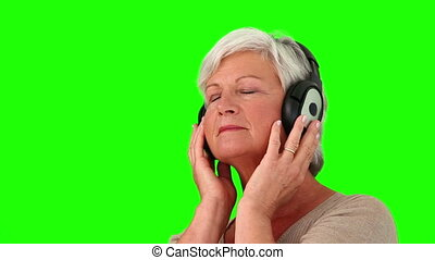 Retired woman listening to music with a headphones
