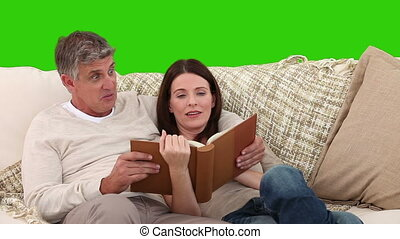 Nice elderly couple looking at an album on their sofa...