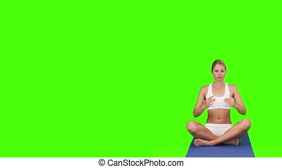 Blond woman doing yoga on a ground cloth