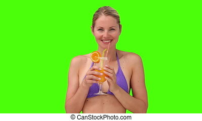 Blond woman in purple swimsuit sipping a cocktail