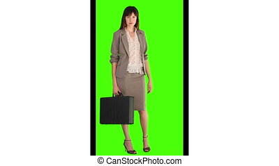 Brunette woman in suit holding a briefcase against a green...