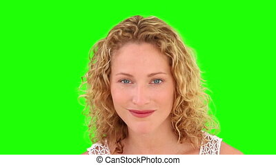 Curly-haired woman plucking off her eyebrow against a green...