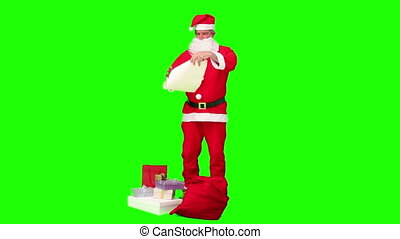 Santa Claus looking at his gift list against a green screen