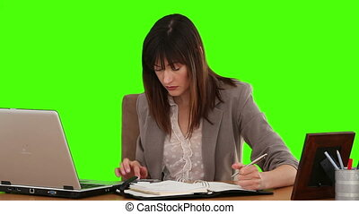 Businesswoman calculating her bills at her desk - Chroma-key...