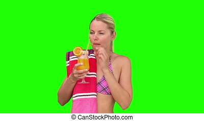 Wonderful woman in swimsuit sipping a cocktail against a...